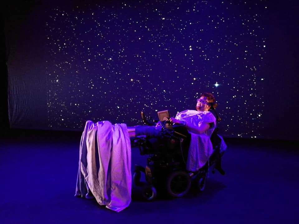 The background is dark blue with stars. In the foreground is a person in a hospital bed.