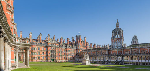 It is a sunny day. The sky is blue. A red-brick building starts on the left of the image, and curves round across the middle, with green grass in front of it. The building looks very grand.