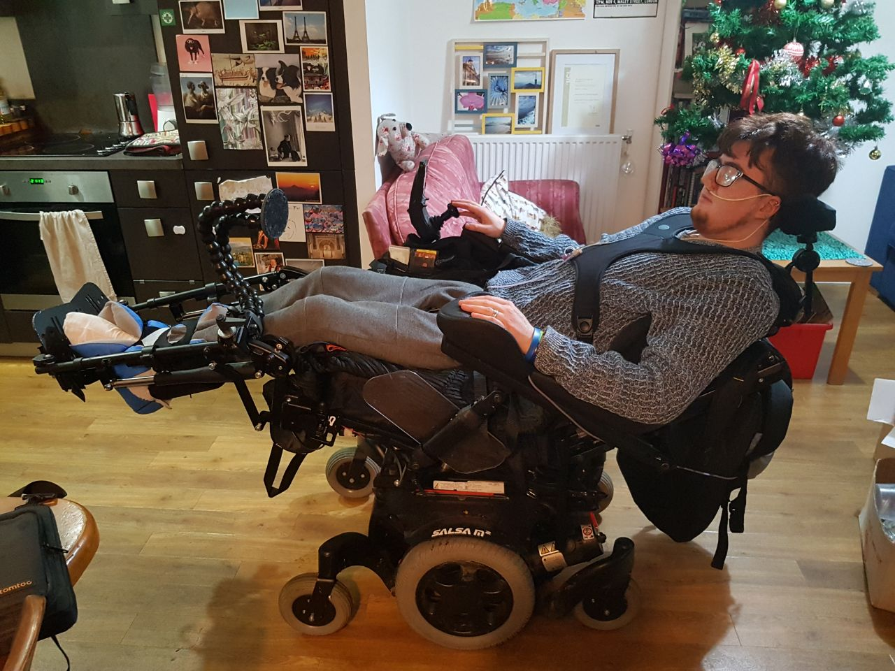 A young adult with dark red hair is reclined in an electric wheelchair. They are wearing a blue jumper