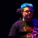 "A person is seated. A wheelchair headrest is visible behind them. The image is dark, but their hair is a bright blue. Their t-shirt is blace, and says ""PISS ON PITY"" in bright pink. They are wearing a microphone and glasses."