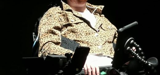 A white person with dark red hair sits in a black electric wheelchair against a black background. They are wearing pink jeans and a leopard print jacket