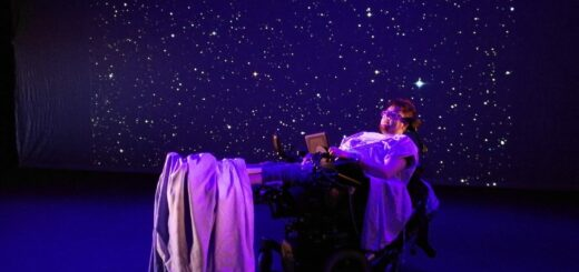 The picture has a dark background with white pinpricks that are stars. Jamie is lying in a hospital bed, bathed in piunk and blue light.