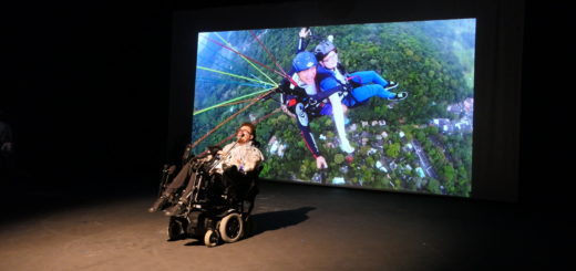 image of me on a stage in front of a film of me paragliding