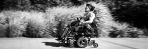A black and white photo showing a white person in an electric wheelchair in the centre of the photo. Behind the person and along the length of the image are blurred bushes, showing that the electric wheelchair is moving rapidly.