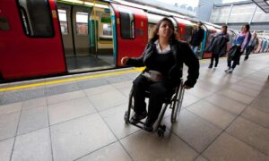 A woman in a manual wheelchair on a London Underground platform
