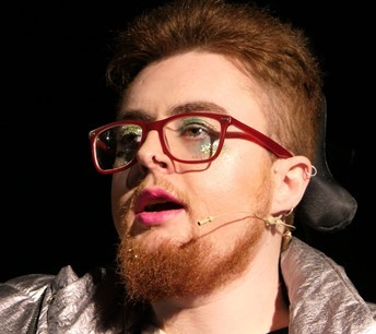 Jamie with a red beard, glasses, and lipstick, wearing green eyeshadow and a silver jacket, clearly performing